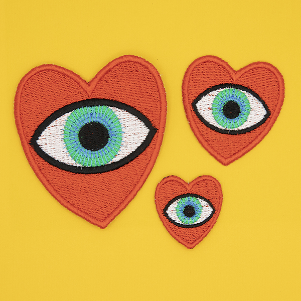 three embroidered patches, all read hearts with blue eye in the centre. Patches are large, medium and small. Displayed in a group on a sunshine yellow background.