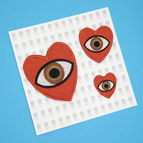 three embroidered patches, all read hearts with brown eye in the centre. Patches are large, medium and small. Displayed in a gift card which features tiny images of The Unruly Stitch logo on a white background.