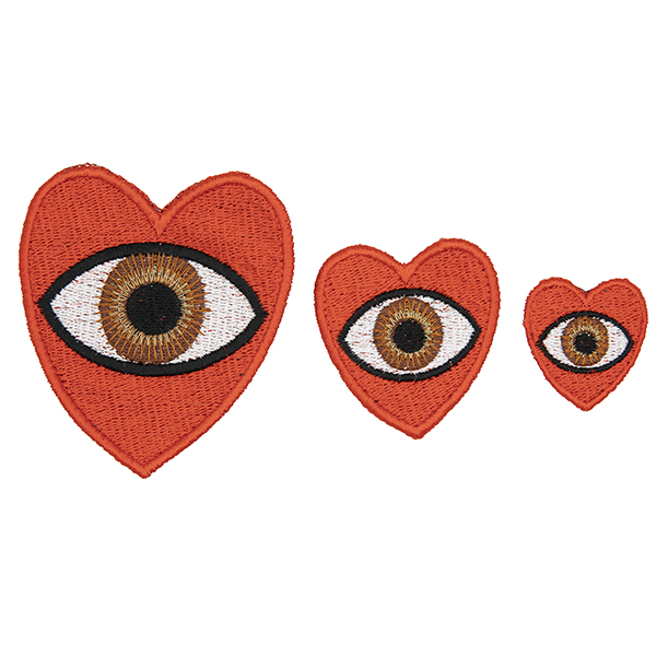three embroidered patches, all read hearts with brown eye in the centre. Patches are large, medium and small. Displayed in a horizontal line on a white background.