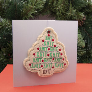cream felt ornament, Christmas tree shape embroidered with KNIT, KNIT, KNIT in green and red fairy lights, shown standing on a red surface with a fir wreath in the background