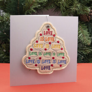 cream felt ornament, Christmas tree shape embroidered with LOVE IS LOVE in pride rainbow colours and red fairy lights , shown standing on a red surface with a fir wreath in the background
