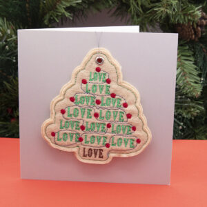 cream felt ornament, Christmas tree shape embroidered with LOVE, LOVE, LOVE in green and red fairy lights, shown standing on a red surface with a fir wreath in the background